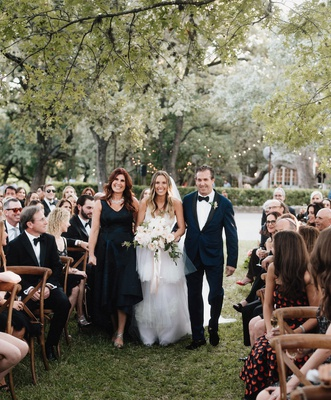 bride with mother of bride and father of bride in navy blue wood chairs grass aisle outdoor ceremony
