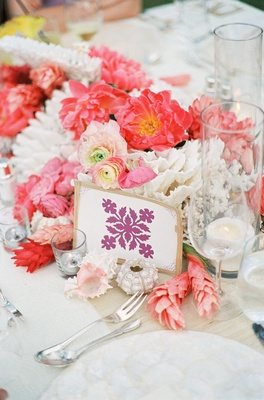 Motif table card surrounded by pink flowers and shells