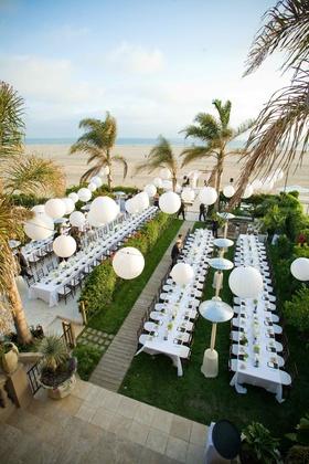 Beach wedding reception with white paper lantern decorations