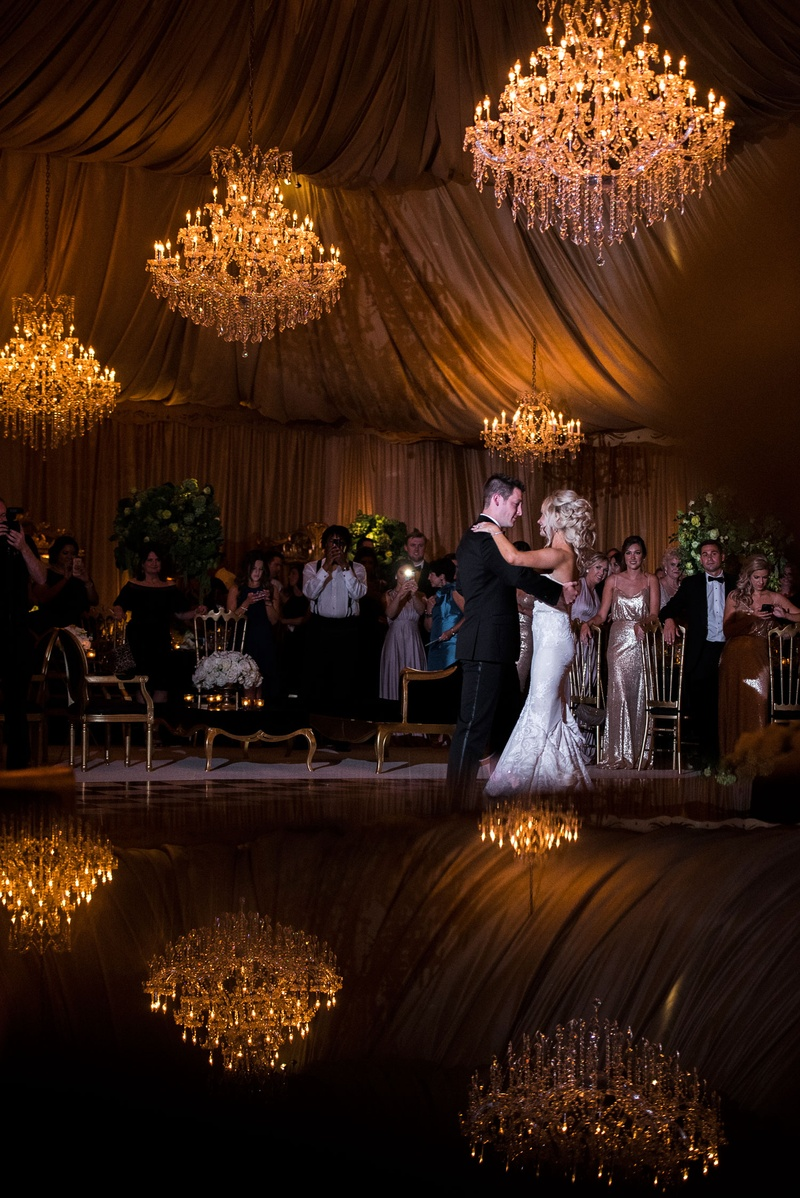 Wedding reception first dance on reflective dance floor chandeliers hanging from top of tent