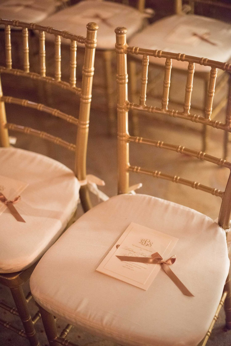 wedding ceremony gold chairs white cushions monogram ceremony program gold ribbon