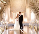 Bride in a strapless Pnina Tornai dress, groom in a black tuxedo at Jewish wedding ceremony site