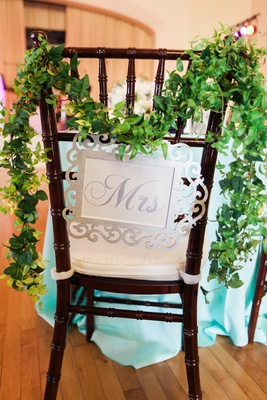 Wedding reception with bride's seat with silver Mrs. sign and garland of leaves