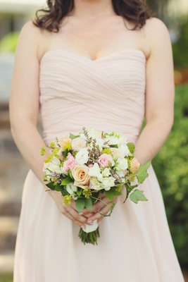 Woman in champagne dress holding freshly picked flowers