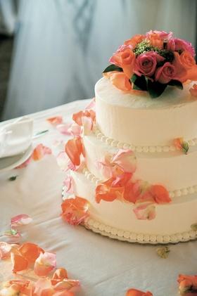 Ivory wedding cake topped with orange roses