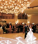 Bride and groom have their first dance on a custom-made floor beneath a floral chandelier