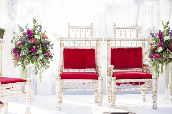 south asian wedding inspiration, red cushions on metallic chairs under mandap