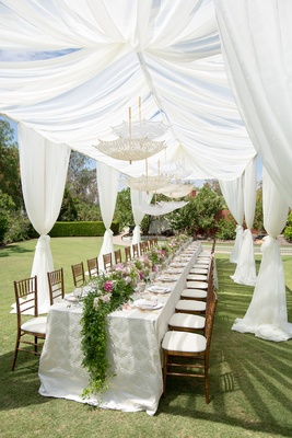 long table with greenery and flower table runner with lace parasols hanging from sheer white drapes outdoor wedding shower