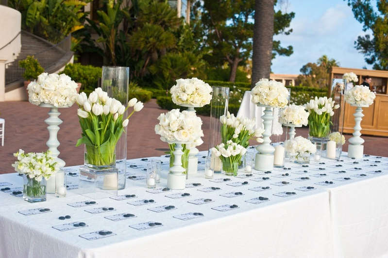 Seating cards on table with white flower arrangements