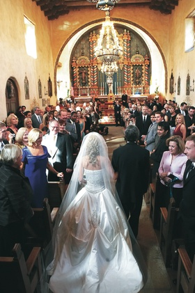 Bride walking down aisle with father in church