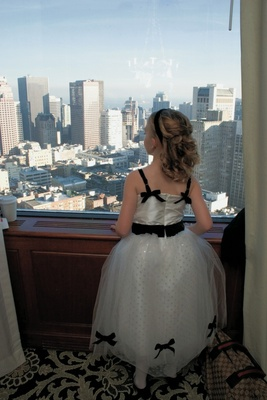Flower girl in white and black dress looks at San Fran skyline