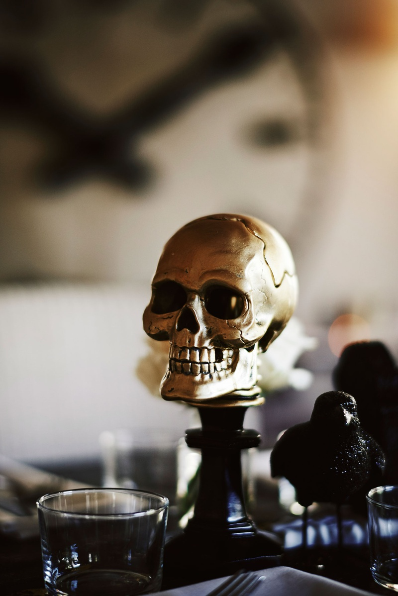 halloween wedding ideas gold skull on top of candlestick and black raven crow