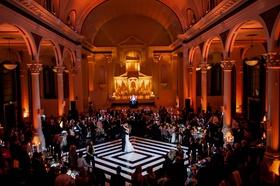 Red orange lighting at vibiana as bride and groom dance on white and black dance floor diamond