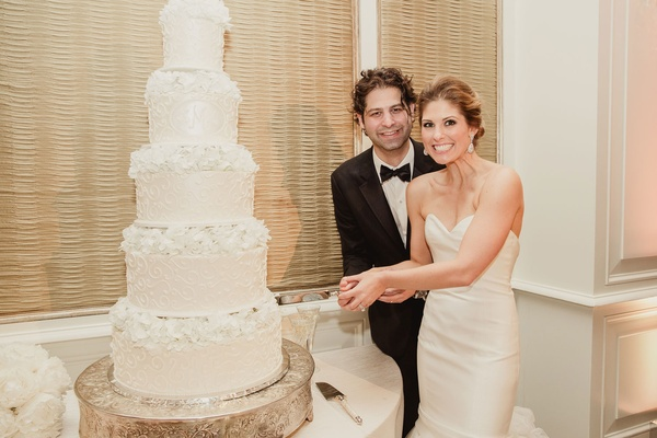 Bride in strapless wedding dress sweetheart neckline groom in suit with bow tie cutting into cake