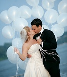 bride and groom kiss while holding balloons