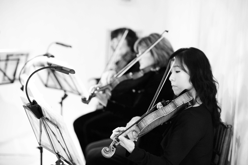 Black and white photo of women playing violin