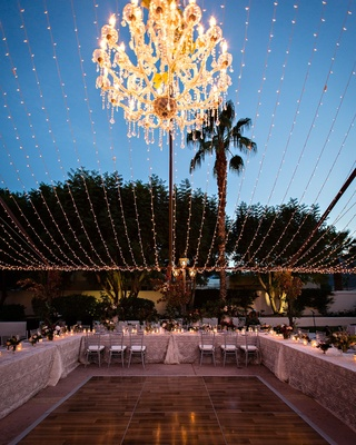 Reception tables around dance floor string lights silver chairs u shape low centerpieces