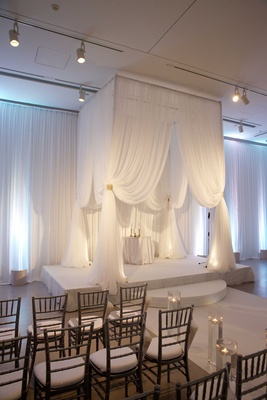 White drapery on four poster wedding structure in ballroom