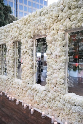 wedding reception white hydrangea rose flower wall mirror seating chart etched with names candles