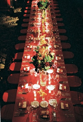 Long red table with clear chargers, candles, and floewrs