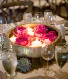 wooden and gold bowl with floating candles and bright pink peonies