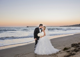 bride in full ruffled ball gown, groom in tuxedo, bride and groom kiss on beach at sunset