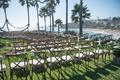 Seaside wedding ceremony in Laguna Beach residence, rustic chairs, white flowers, greenery