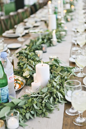 Farm wedding reception table with leafy garlands, pillar candles on a tan runner