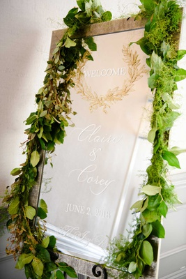 wedding reception welcome sign mirror signage greenery fresh leaves moss gold laurel wreath
