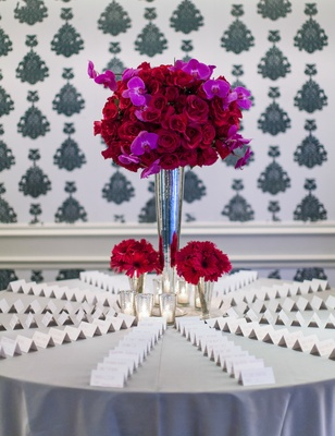 Escort cards on silver table with red and fuchsia flower arrangement