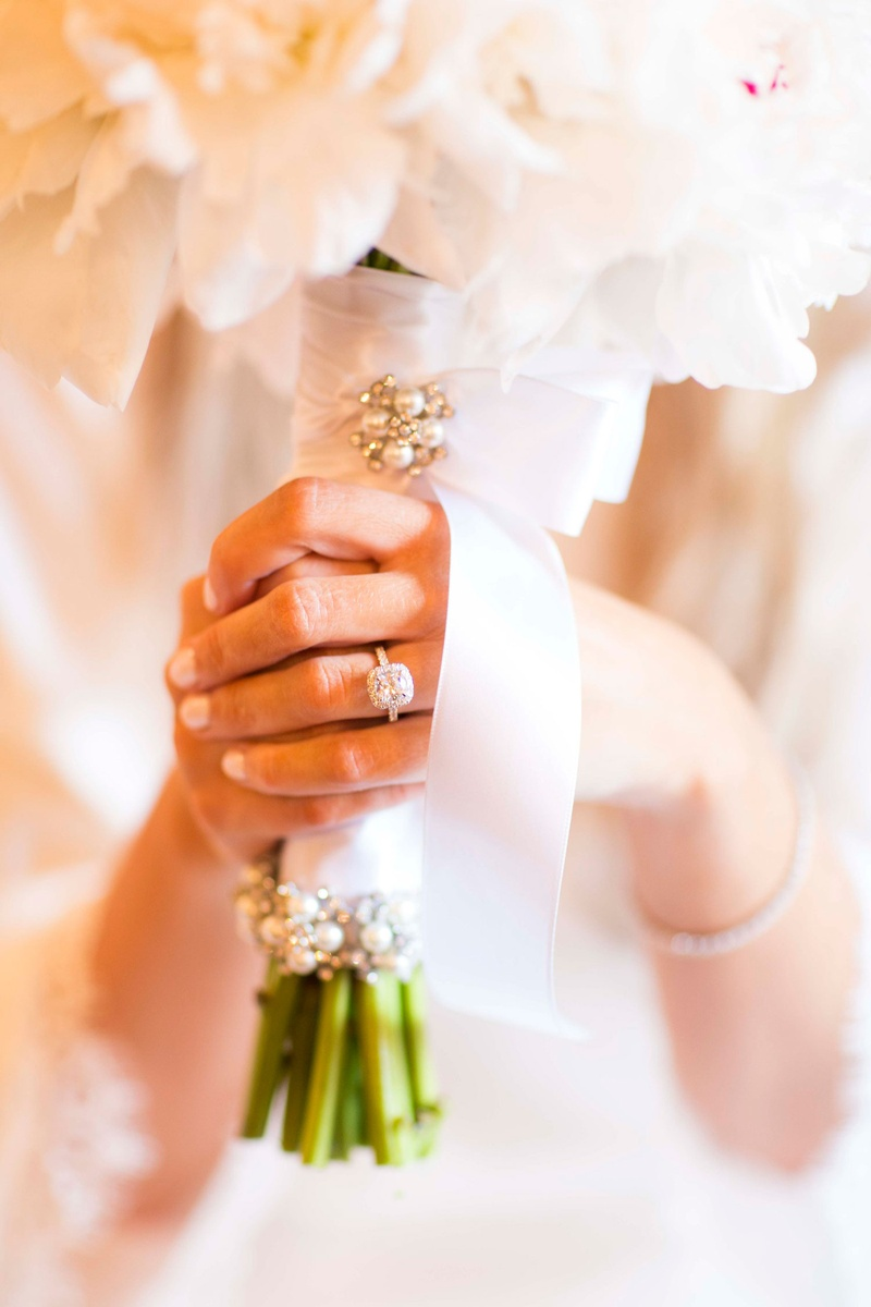 Halo engagement ring neutral manicure clutching bouquet white ribbon and pearl pins