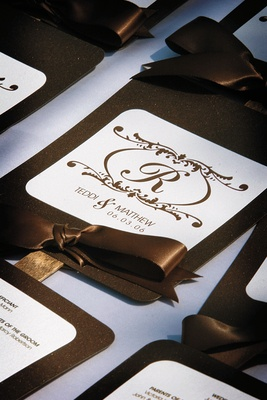 wedding program with brown lettering and ribbon