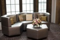 Wedding lounge with contemporary sofas, octagon table, gold patterned throw pillows