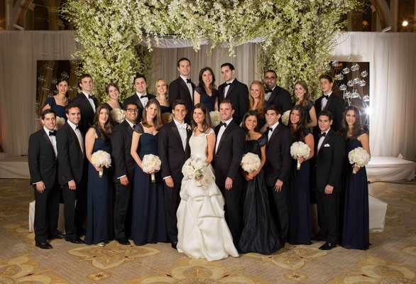 Bride in a Monique Lhuillier gown and groom in a black tuxedo with their bridal party