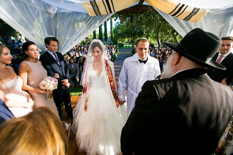 a jewish couple wearing traditional garb marrying under chuppah