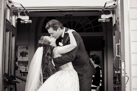 Black and white photo of bride and groom kissing on outside of church doors after ceremony veil long