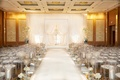all white wedding ceremony with white drapery arches and clear ghost chairs with white cushions