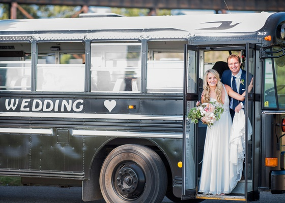 bride and groom on school bus painted black and personalized with their names and a heart transport
