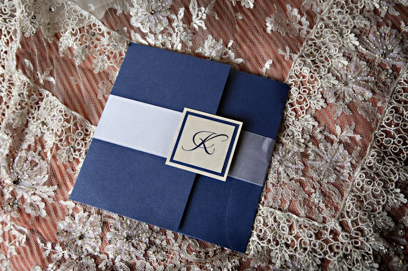 Wedding invitation with a blue exterior, ribbon, and monogrammed seal