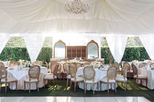 White draped tent with chandelier and rustic upholstered chairs