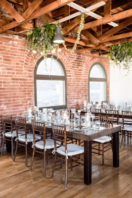 Wedding reception wood tables wood chairs mirror runner brick wall greenery on ceiling can lights