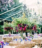 Tall wedding centerpiece with wrap around garland, verdure, pink rose, purple flower, blue goblets