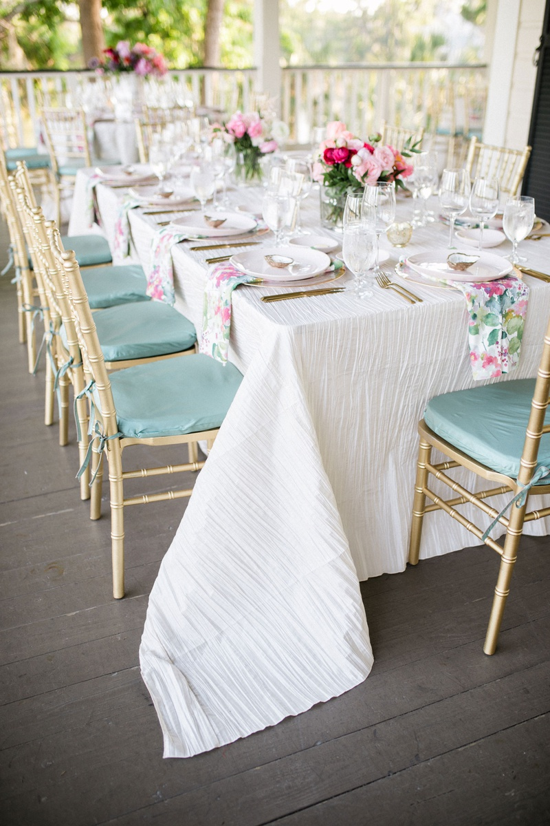 wedding reception on porch white linen sage green mint cushions gold chairs pink pastel centerpiece