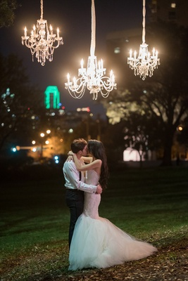 bride in nardos deisgns lace mermaid gown kisses groom under outdoor chandeliers