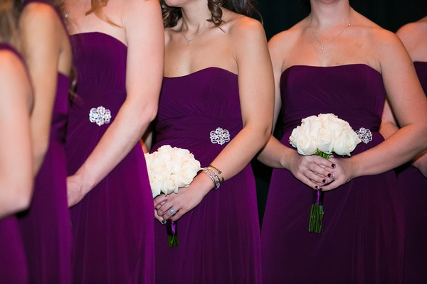 Bridesmaids in strapless purple dresses with brooches at waist holding white rose bouquets
