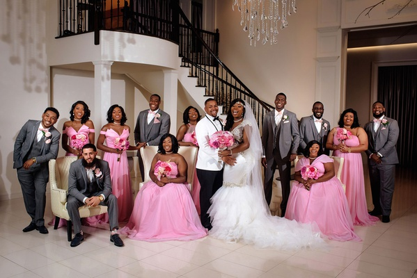 bride in mermaid dress groom in white tuxedo bridesmaids in pink mismatch dresses groomsmen in grey