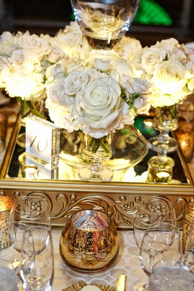 white flowers mirrored stand with gold detailing and glass table number small candle