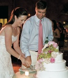 Couple cuts four layer cake at reception
