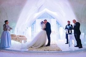 bride and groom kiss ice castle wedding ceremony fur rug ice altar pews unique wedding venue