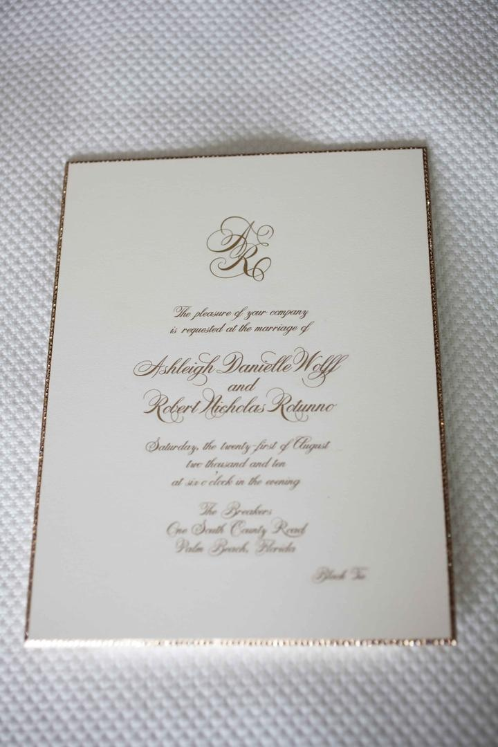 Ivory wedding invite with gold script and border